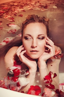 Jovem mulher com cabelo vermelho tomar banho de espuma com vela.