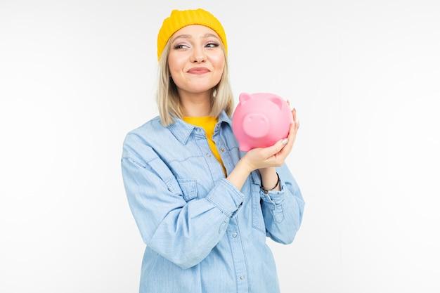 Jovem mulher com cabelos brancos em uma camisa azul com um banco para salvar finanças em um fundo branco do estúdio com espaço da cópia