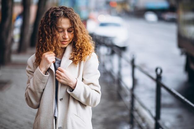 Jovem mulher com cabelos cacheados fora da rua