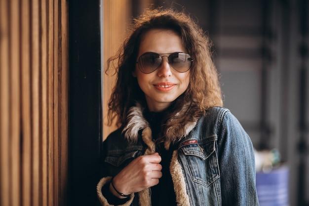Jovem mulher com cabelos cacheados na jaqueta jeans