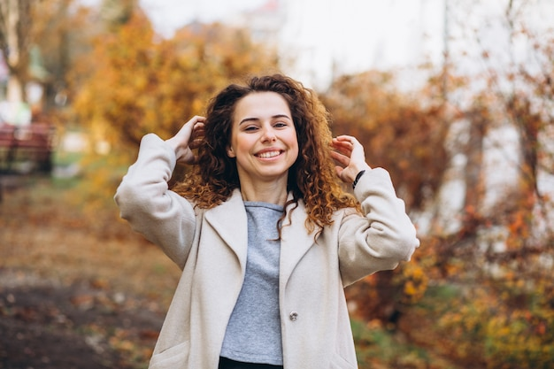 Jovem mulher com cabelos cacheados no parque