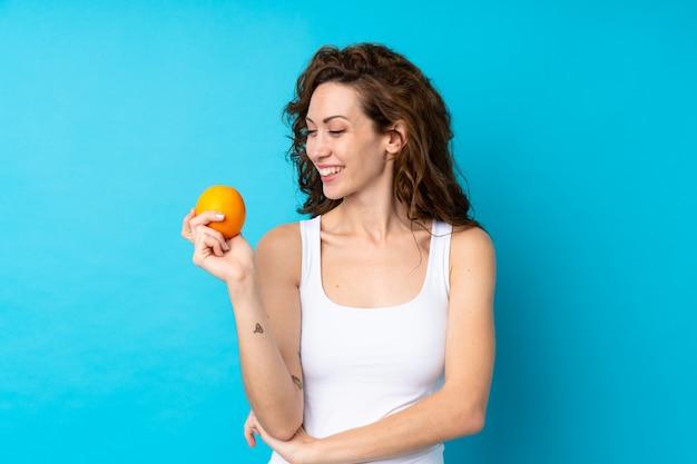 Jovem mulher com cabelos cacheados, segurando um laranja azul