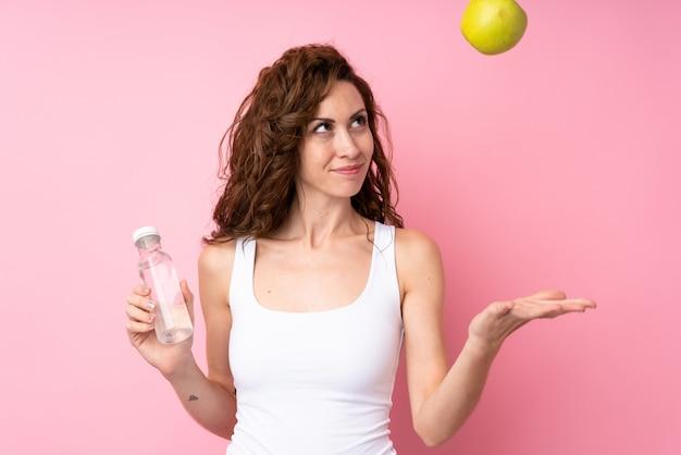 Jovem mulher com cabelos cacheados, segurando uma maçã e uma garrafa de água sobre a parede rosa isolada