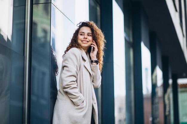Jovem mulher com cabelos cacheados, usando o telefone na rua