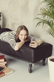 Jovem mulher com cabelos cacheados, usando seu smartphone