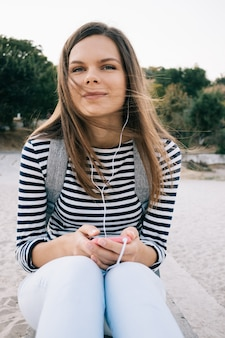 Jovem mulher com cabelos castanhos compridos em uma camiseta listrada e jeans, ouvindo música com fones de ouvido na praia