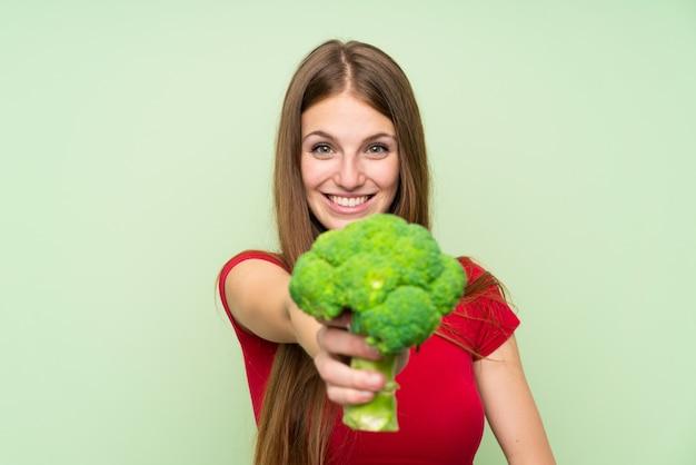 Jovem mulher com cabelos compridos, segurando um brócolis