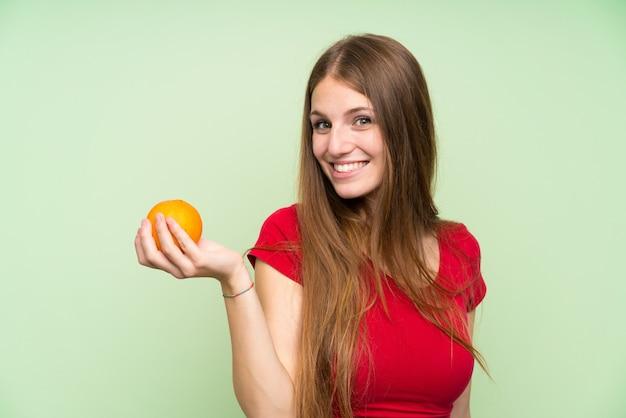 Jovem mulher com cabelos compridos, segurando uma laranja