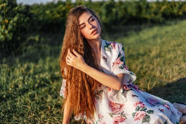 Jovem mulher com cabelos longos cacheados, morena, rosto de sardas, com maquiagem e olhos verdes, em vestido branco claro posando