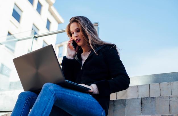 Jovem mulher com cabelos longos e jaqueta preta fala ao telefone e usa o laptop ao ar livre