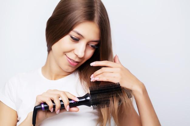 Jovem mulher com cabelos luxuosos endireita-o com um ferro de frisar