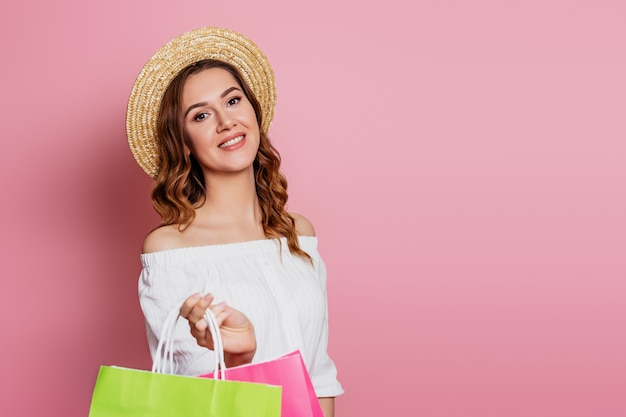 Jovem mulher com cabelos ondulados em um chapéu de palha e vestido vintage com uma rosa e verdes sacolas em uma parede rosa. garota sorri e faz o conceito de venda de compras on-line