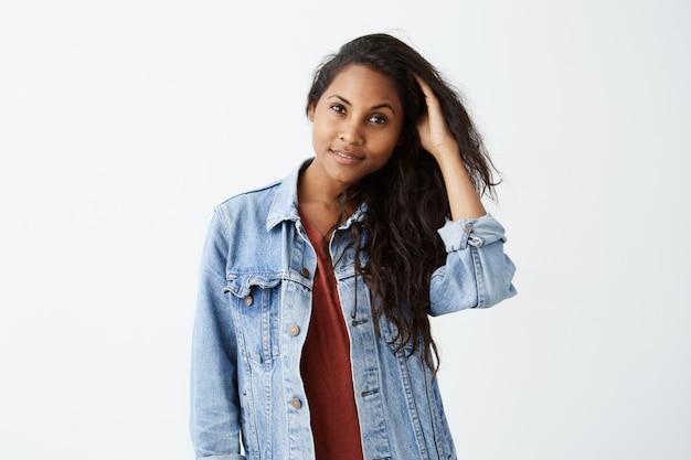 Jovem mulher com cabelos ondulados escuros na jaqueta jeans e camiseta vermelha a sorrir, posando e brincando com o cabelo dela. garota afro-americana vestida casualmente alegremente.