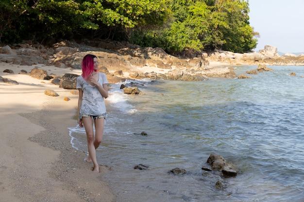 Jovem mulher com cabelos rosa vibrantes, andando perto do mar ou oceano.