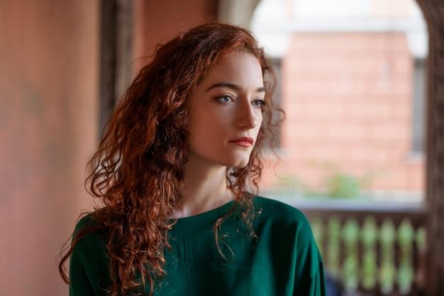 Jovem mulher com cabelos ruivos e sardas, na rua perto do prédio