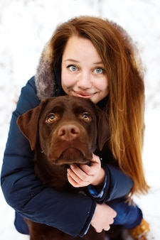 Jovem mulher com cachorro labrador na floresta de inverno