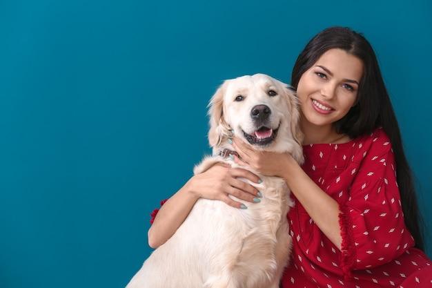 Jovem mulher com cachorro na cor de fundo. amizade entre animal de estimação e dono