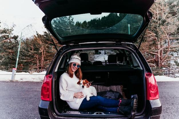 Jovem mulher com cachorro no carro se divertindo. montanha nevada.