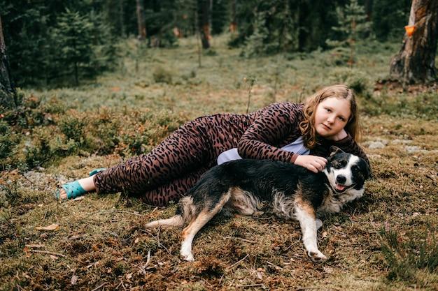 Jovem mulher com cachorro posando na floresta
