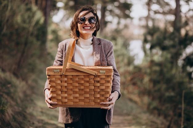 Jovem mulher com caixa de piquenique na floresta