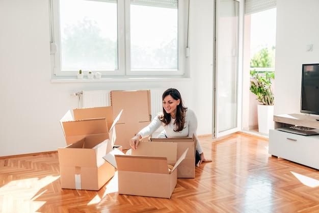 Jovem mulher com caixas da caixa do cartão com os pertences pessoais na casa nova.