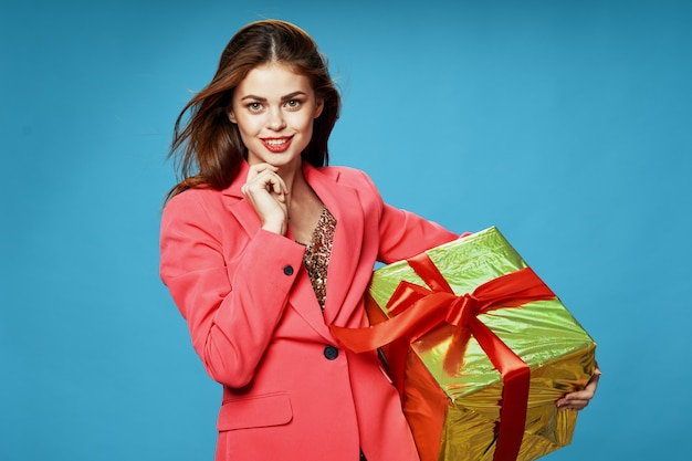 Jovem mulher com caixas de presentes nas mãos dela, sobre um fundo colorido em roupas bonitas, vendendo presentes, feliz natal e ano novo