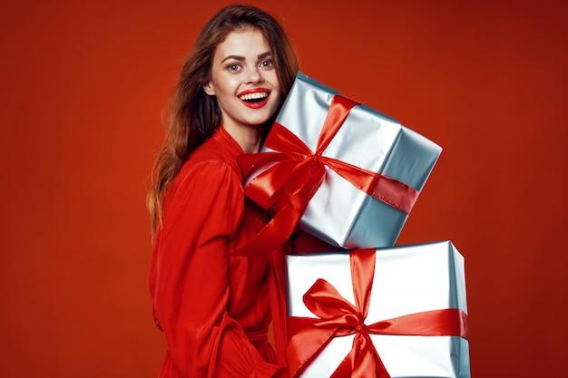 Jovem mulher com caixas de presentes nas mãos em roupas bonitas, vendendo presentes, feliz natal e ano novo