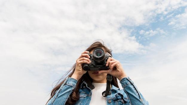Jovem mulher com câmera tirando fotos