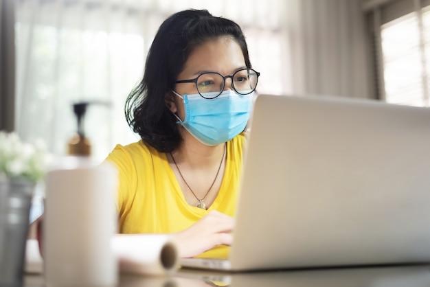 Jovem mulher com camisa amarela usar máscara cirúrgica, trabalhando em casa durante o vírus da pandemia. covid 19, coronavírus, assistência médica, prevenção, proteção.