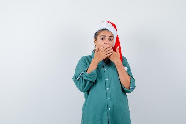 Jovem mulher com camisa, chapéu de papai noel, cobrindo a boca com as mãos e olhando horrorizada, vista frontal.