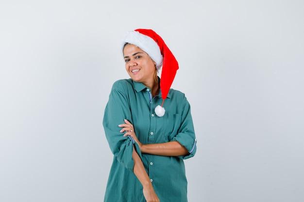 Jovem mulher com camisa, chapéu de papai noel com a mão no braço enquanto sorrindo e olhando alegre, vista frontal.