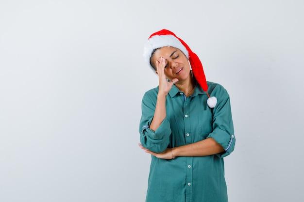 Jovem mulher com camisa, chapéu de papai noel, mantendo a mão na cabeça e parecendo cansada, vista frontal.