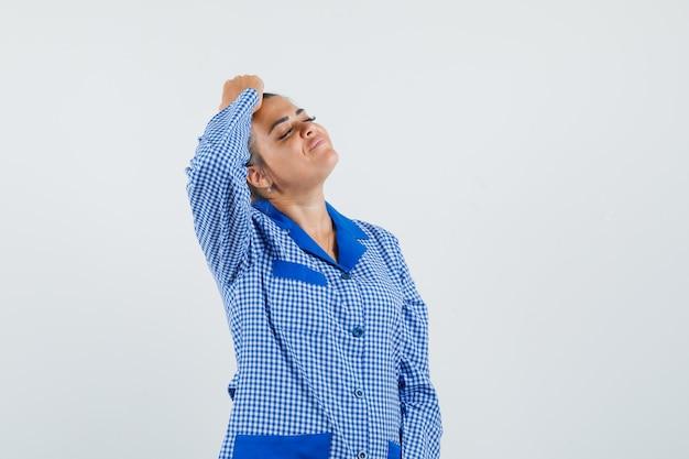 Jovem mulher com camisa de pijama guingão azul, colocando a mão na cabeça e olhando bonita, vista frontal.