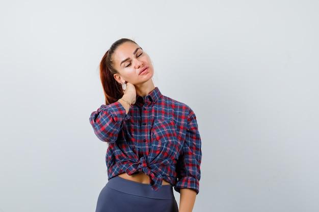 Jovem mulher com camisa quadriculada, calça com a mão no pescoço e parecendo exausta, vista frontal.