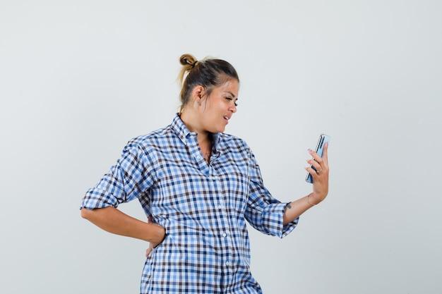 Jovem mulher com camisa quadriculada, fazendo videochamada no telefone.
