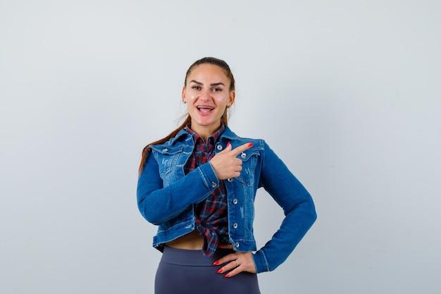 Jovem mulher com camisa quadriculada, jaqueta, calça apontando para o lado direito, mantendo a mão no quadril e olhando espantada, vista frontal.