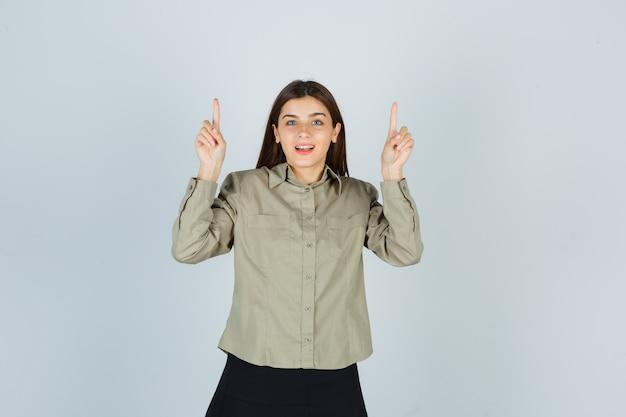 Jovem mulher com camisa, saia apontando para cima e parecendo feliz