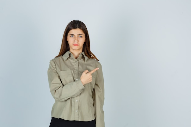 Jovem mulher com camisa, saia apontando para o canto superior direito, curvando o lábio inferior e parecendo ofendida, vista frontal.