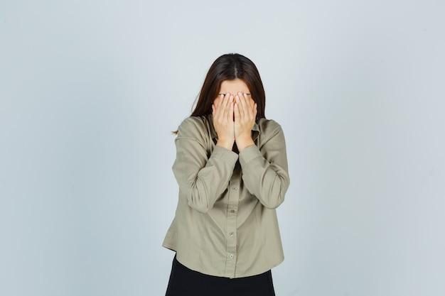 Jovem mulher com camisa, saia cobrindo o rosto com as mãos e parecendo deprimida, vista frontal.