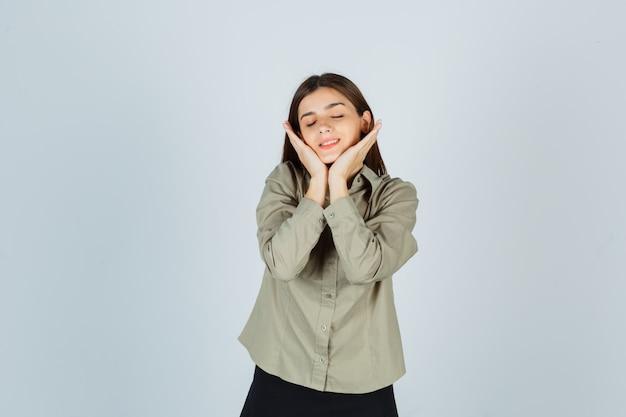Jovem mulher com camisa, saia, mantendo as mãos sob o queixo e parecendo relaxada, vista frontal.