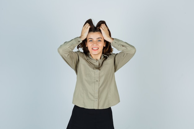Jovem mulher com camisa, saia segurando a cabeça com as mãos e parecendo feliz
