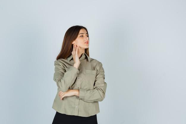 Jovem mulher com camisa, saia tocando a pele do pescoço enquanto olha para o lado e parece pensativa, vista frontal.