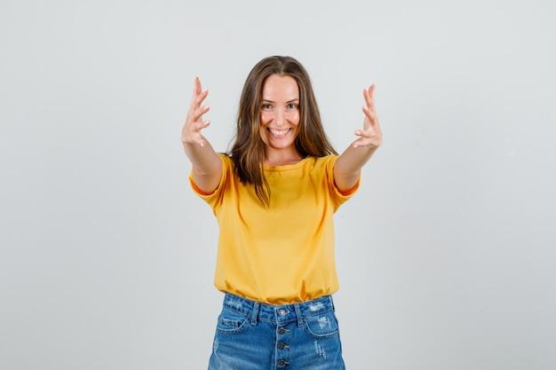 Jovem mulher com camiseta e shorts convidando a vir com as mãos e parecendo alegre