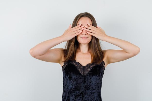 Jovem mulher com camiseta preta cobrindo os olhos com as mãos e parecendo animada
