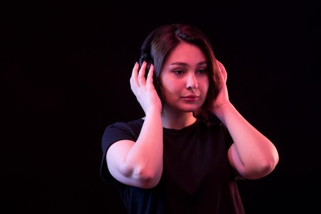 Jovem mulher com camiseta preta usando fones de ouvido