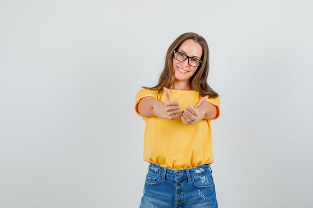 Jovem mulher com camiseta, shorts e óculos mostrando os polegares para cima e sorrindo