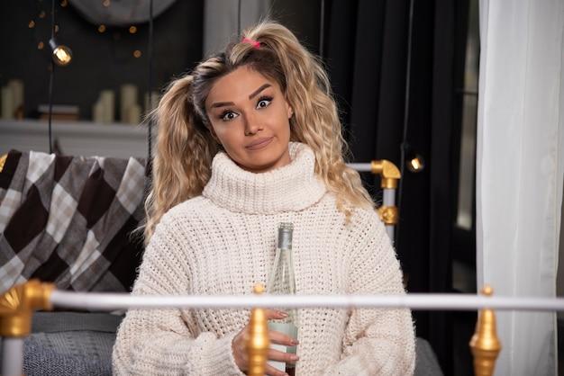 Jovem mulher com camisola de malha, posando com champanhe.