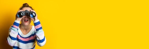 Jovem mulher com camisola olhando através de binóculos em fundo amarelo.