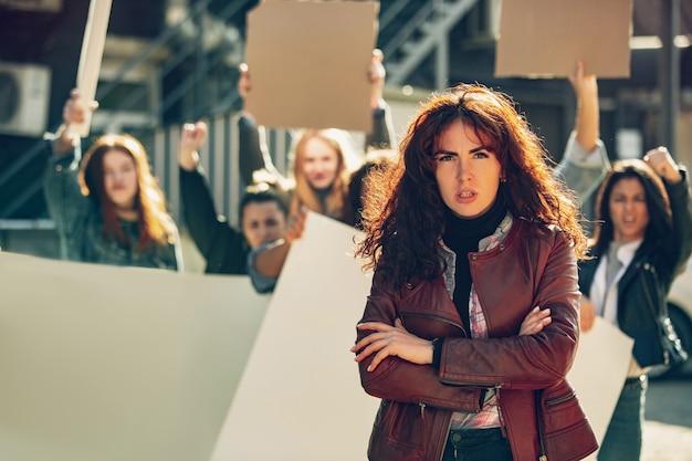 Jovem mulher com cara de zangada na frente de pessoas que protestam sobre os direitos das mulheres e a igualdade nas ruas. reunião sobre problemas no local de trabalho, pressão masculina, violência doméstica, assédio. copyspace.