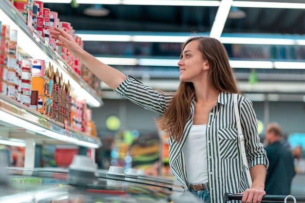 Jovem mulher com carrinho de compras escolhe e compra de produtos no supermercado